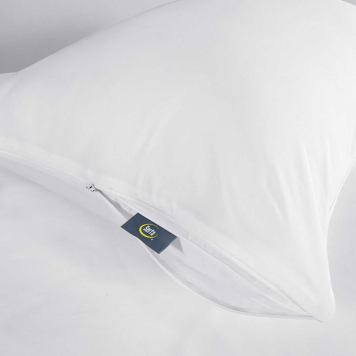 Serta Chill Luxe Pillow Protector - pillow on bed, showing tag detail