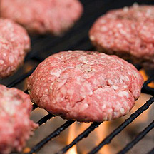 Raw burger patty on the grill